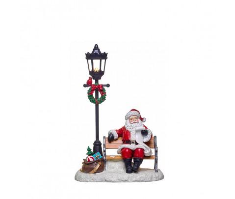Papa Noel sentado en un banco con farola